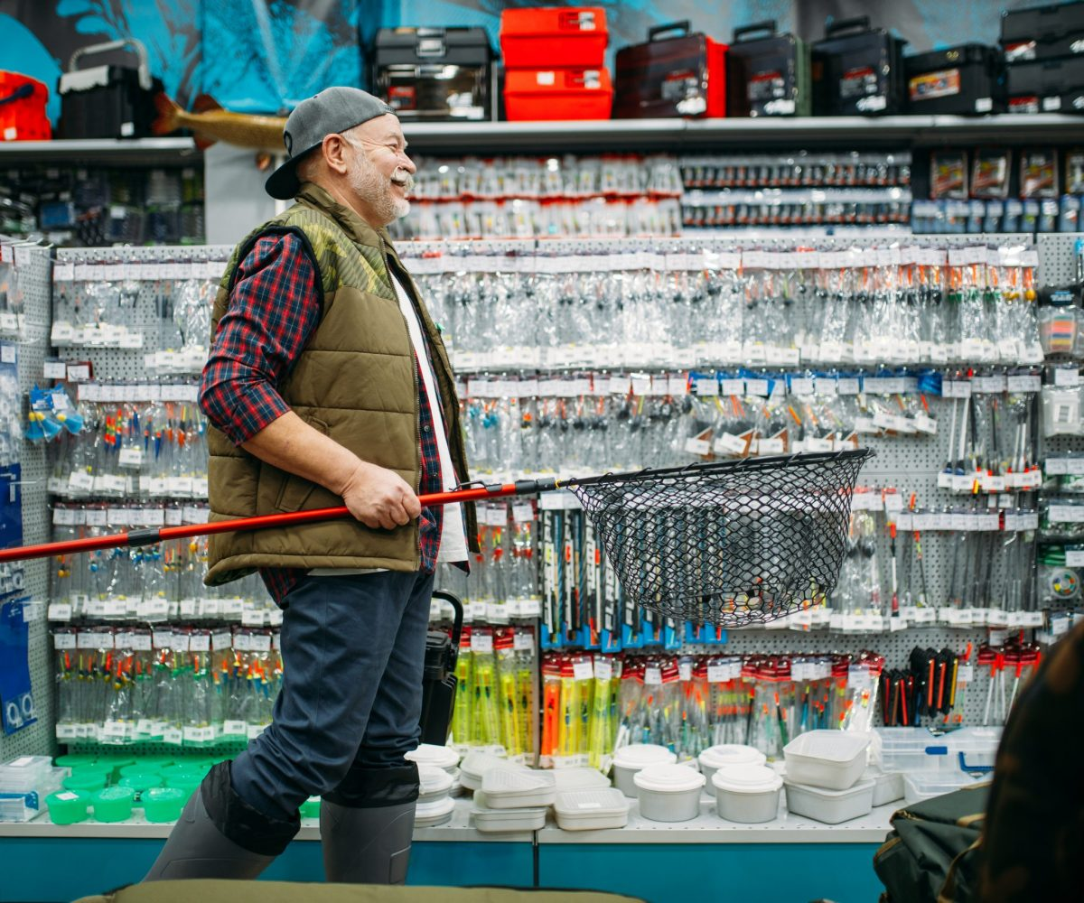 Fisherman with net and toolbox in fishing shop, hooks and baubles on background. Equipment and tools for fish catching and hunting, accessory choice on showcase in store, bait assortment